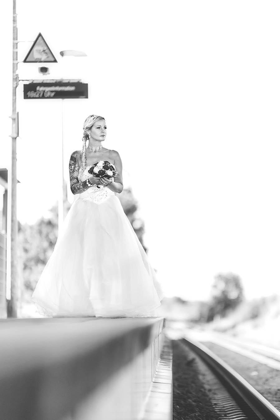 Braut wartet am Bahngleis mit ihrem Kleid und Brautstrauß auf ihren Bräutigam