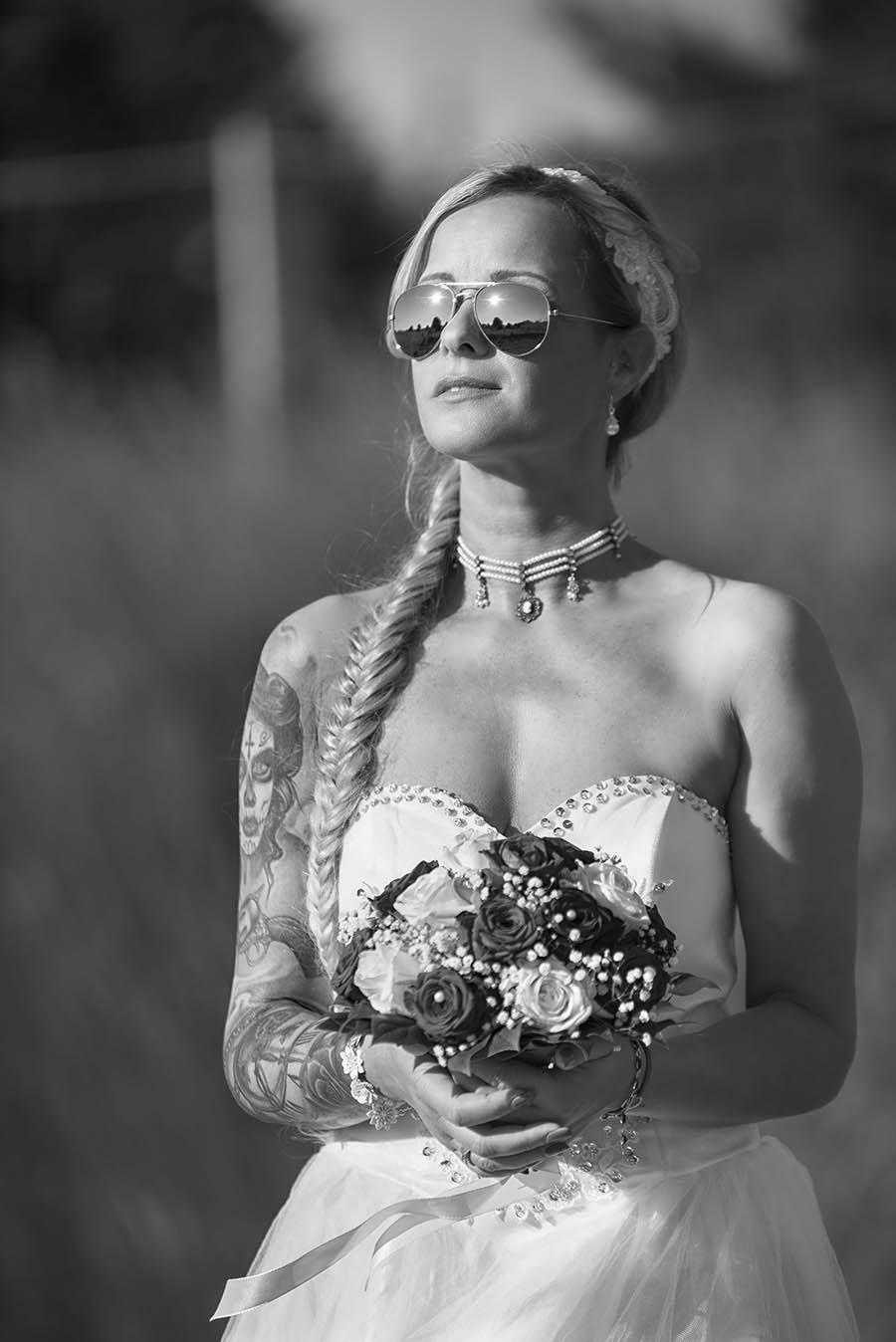 Braut steht mit Sonnenbrille am Gleis
